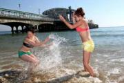 17 yr old Poole girls Alicia Jones (left) and Leah Twist have some fun in the sea at Bournemouth Pier. Picture: Sally Adams.