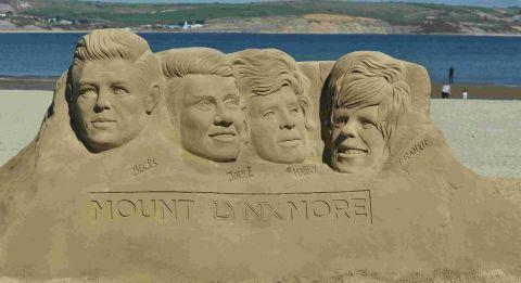 Dorset Beaches: THAT'S SANDY: Four celebrity heads, created on Weymouth Beach from 40 tonnes of sand to announce a new hair care range
